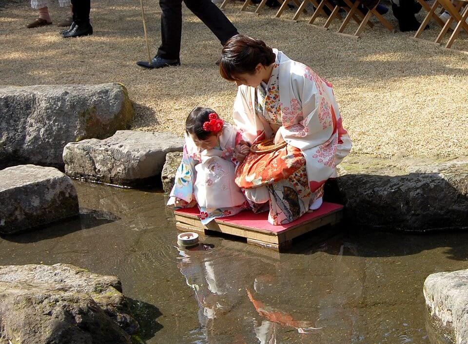 Japanese mother and daughter floating doll down river